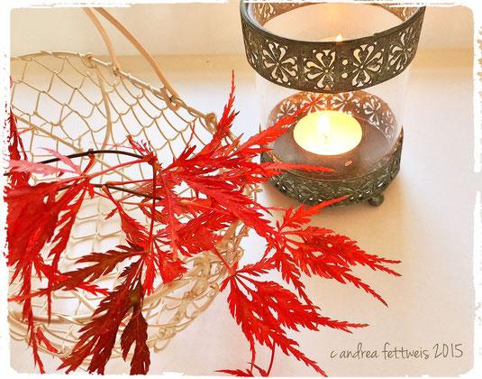 Herbstdeko mit Ahornzweig im Körbchen und Windlicht