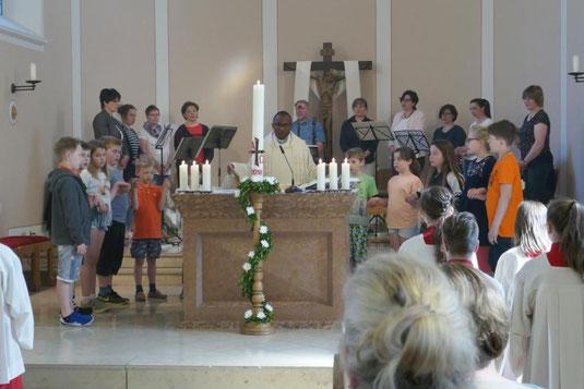 Father Dominik Ekweariri am Altar, zukünftige Erstkommunionkinder und Kreis für junge Musik