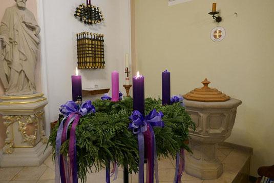Adventskranz in St. Josef mit drei violetten und einer rosa Kerze