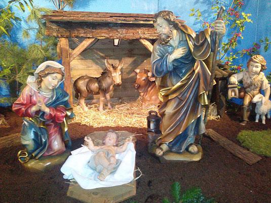 Foto mit dem Jesuskind in der Krippe, umgeben von Maria, Josef und den Eseln im Stall