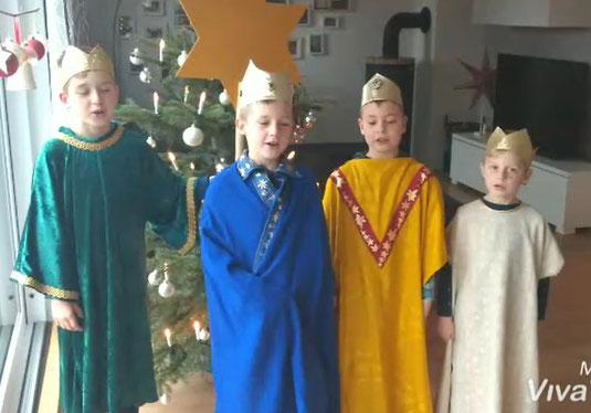 Foto mit vier Sternsingern in einem Wohnhaus
