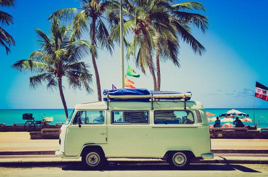 VW-Bus, im Hintergrund Palmen und türkises Meer