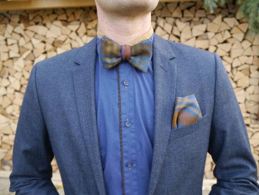 Braune, Blaue, orangene gemusterte Fliege zum Binden - Querbinder auf dunkelblauem Anzug und blau braunem Hemd