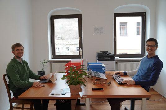 Zwei Männer sitzen an zwei gegenüberliegenden Tischen,