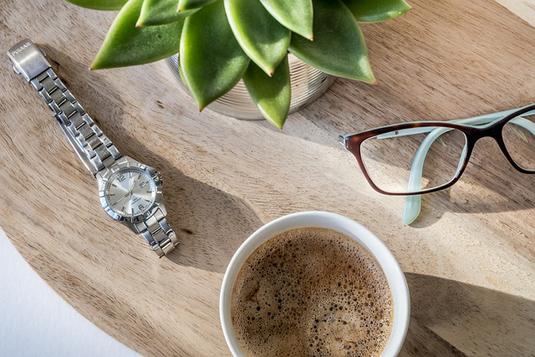 ネクタイの結び目。水色のシャツと青地に茶色のストライプのネクタイ。