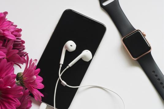パソコンのキーボード。イヤホンとスマートフォン。手帳。