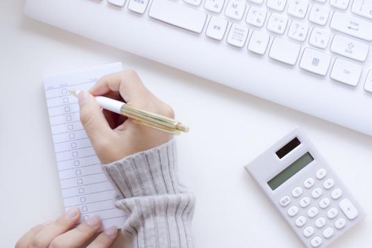 デスクに広げられたノートパソコン、スマホ、ボールペン、電卓、英字の金融新聞。