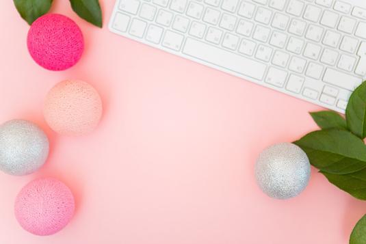 オフィスのデスクでノートパソコンに向かう新人。紺スーツ姿の女性。観葉植物の鉢植え。