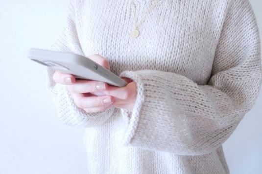 自宅のソファに腰かけてスマートフォンを操作する女性。白のTシャツにモスグリーンのカーディガン姿。