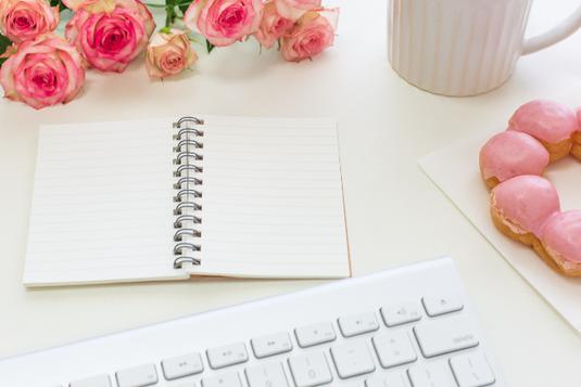 パソコンのキーボードの前に置かれたリングノート。マグカップとストロベリーチョコのドーナッツ。ピンクのバラのブーケ。