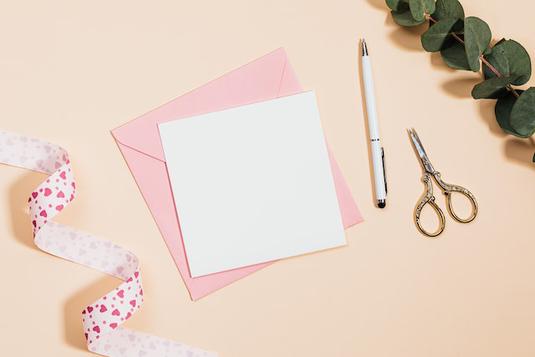 スマートフォンとイヤフォン。パソコンのキーボード。ピンクのダブルクリップ。ピンクのつぼみのバラたち。