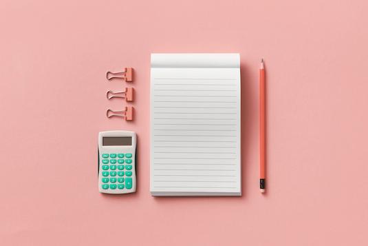 机に広げられた白の電卓とコイン。