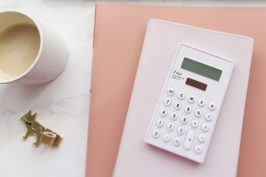 ピンクのノートと手帳のうえに置かれた電卓。コーヒーの入ったマグカップ。