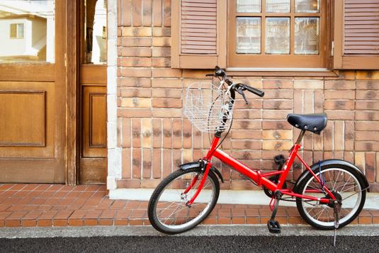 白の自転車を押すパンツルックの女性。自転車通勤。