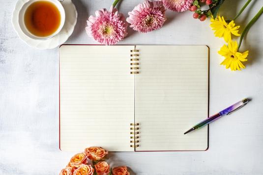白紙の紙とボールペン。ペン立て。黒の表紙のリング式ノート。クリップ。