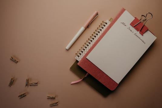 オフィスのデスクで頬杖をつくビジネスウーマン。紺のカーディガン姿。デスクトップ型パソコン。ペン立て。卓上サイズのグリーンの鉢植え。