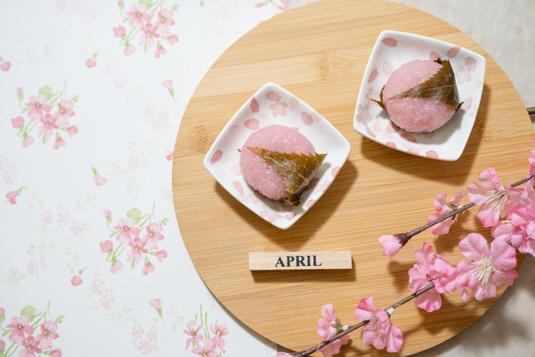 ピンクの手帳のうえに置かれたピンクの腕時計、ピンクゴールドのボールペンとクリップ。ピンクのガーベラのブーケ。