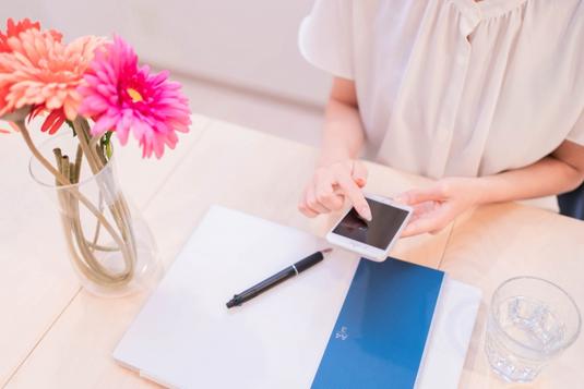 リングノートを広げながら、ペンを持つ手で電卓をたたくビジネスウーマン。傍らにマグカップ。