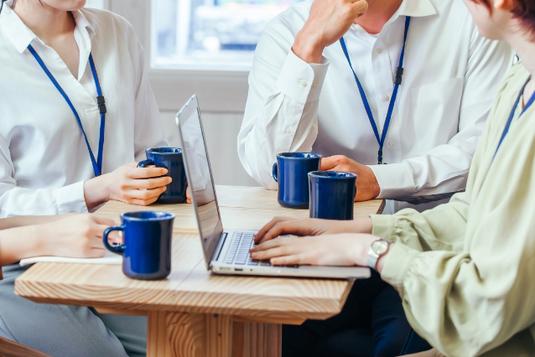 オフィスの打ち合わせ机でコーヒーを飲みながらミーティングする男女4人。ノートパソコンで議事録作成中。