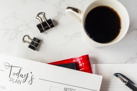 マーブル調のテーブルに置かれた資料と手帳、ボールペン。あぶるクリップ、コーヒーの入ったマグカップ。