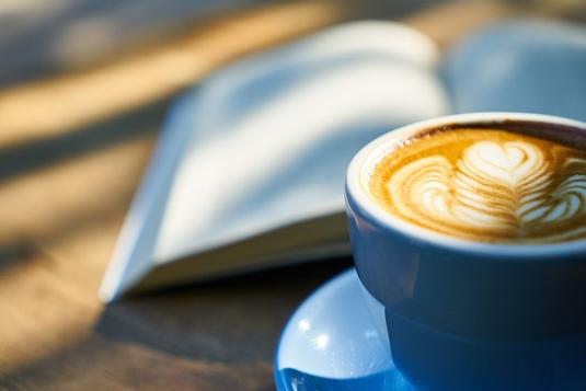 積まれたリングノートとスケジュール帳の上に置かれた白の電卓。ボールペンダブルクリップ。ボールペン。スマホ。