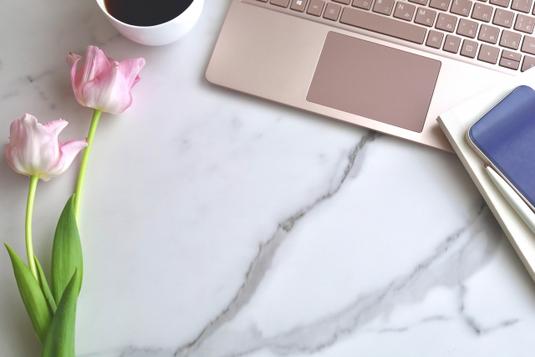 パソコンのキーボードの前に置かれたピンクの腕時計。ゴールドのダブルクリップ。