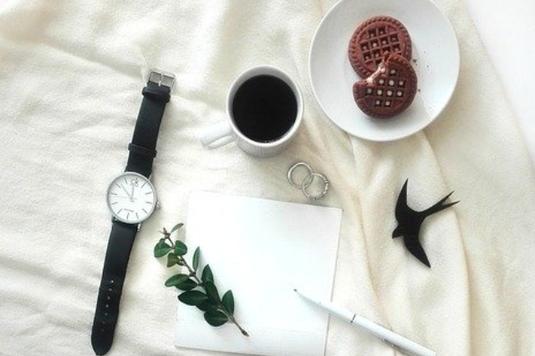 休日のベッド。シーツのうえに置かれたコーヒーの入ったマグカップ。クッキーの皿。腕時計。便箋とペン。