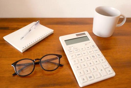 デスクに広げられたメモ帳とボールペン、白の電卓とマグカップ、眼鏡。