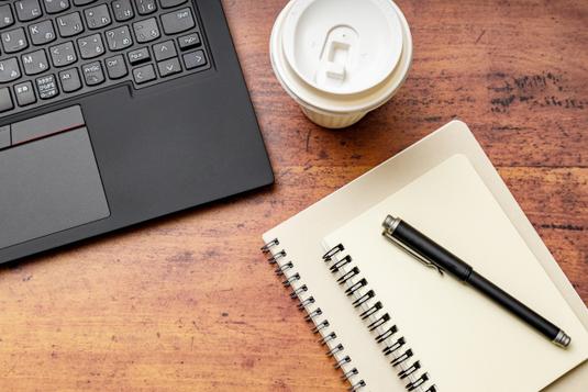 眼鏡、スマホ、電卓、メモ帳。チョコチップクッキーとコーヒーの入ったマグカップ。