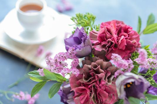 ピンクのノートパソコン。レトロなピンクの置時計。小皿に乗ったハート形のピンクのマカロン。