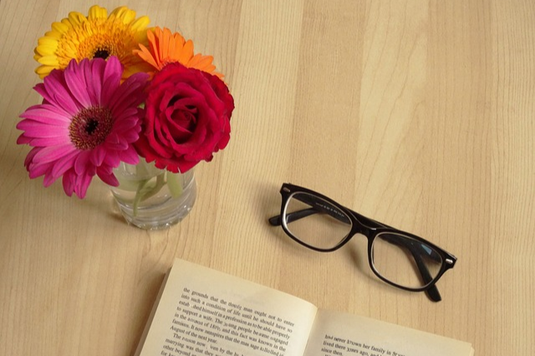 テーブルに置かれた眼鏡と読みかけの本。ガーベラ、デイジー、バラが活けられたガラスの花びん。