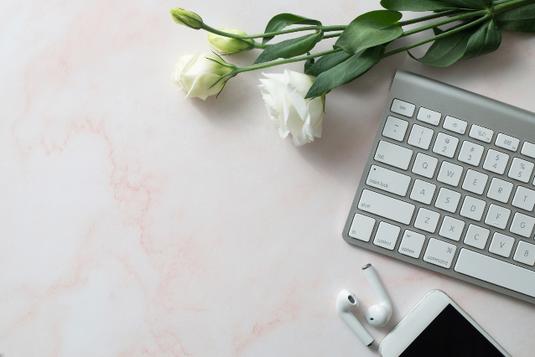 パソコンのキーボード。スマートフォンとイヤフォン。無造作に置かれた白のバラ。
