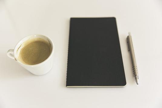 パソコンのキーボードを叩く紺のジャケット姿のビジネスウーマン。