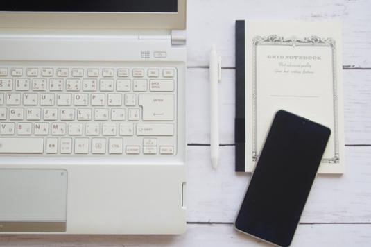 テーブルに広げられたリングノート。メッセージカードとピンクのハサミ。コーヒーの入ったカップ&ソーサ。