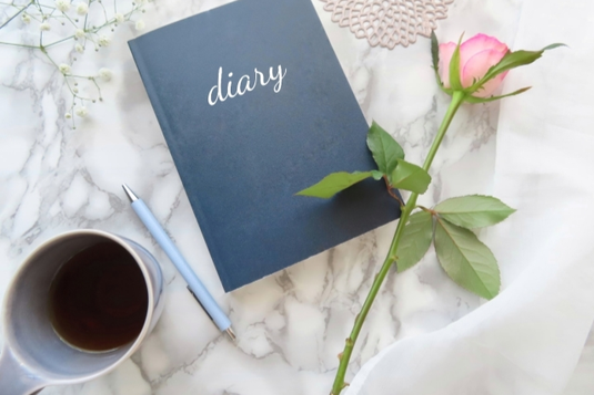 自宅のデスク。木製の日替わりカレンダー。額縁のアート。花柄のノート。レンギョウの花。