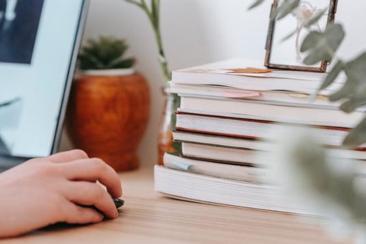パソコンのキーボードとマウスを抱える白シャツにデニム姿の女性。