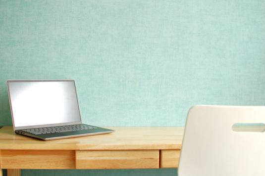 木目調のデスクに広げられたノートパソコン、資料のファイル、ノート、クリップ、付箋、スマホ。コーヒーの入ったマグカップ。