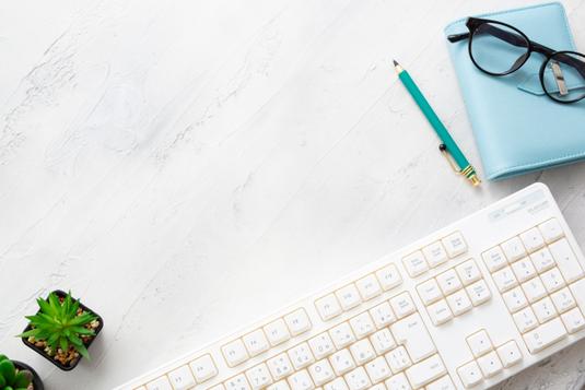 パソコンのキーボードの前に置かれたピンクの腕時計、ゼムクリップがいっぱい入った缶、ゴールドのダブルクリップ。