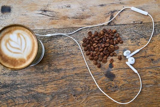 広げられたノートとボールペン。傍らにハートのチャームのネックレス。ピンクのチューリップとモンステラの葉。