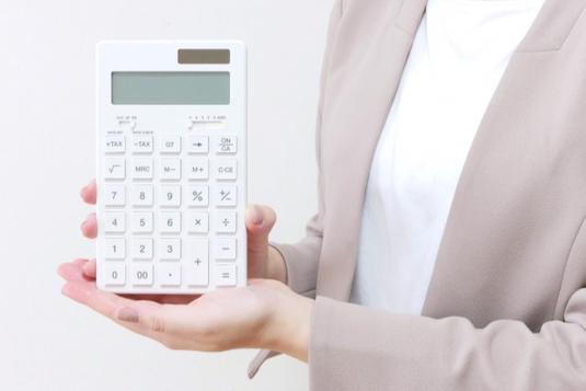 白の電卓を両手で掲げ持つベージュのジャケット姿の女性。