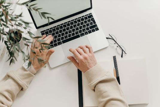 ピンクのノートパソコン。オレンジピンクのガーベラとバラの花。ピンクのメモパッドの上に置かれたピンクの腕時計。