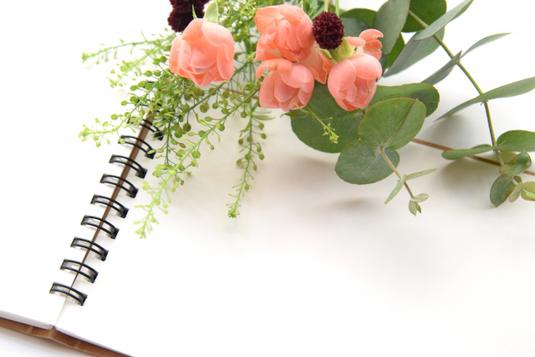 アジサイが活けられた白磁の花びん。読みかけの本のうえに置かれた眼鏡、コーヒーの入ったカップとトレイ。