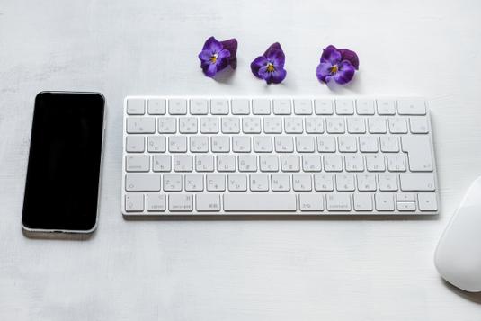 パソコンのキーボード。リングノートの上に置かれた水色の革ベルトの腕時計。白のマーガレットの花。