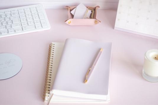 ピンクのノート、メモ帳。ゴールドのボールペンとダブルクリップ。