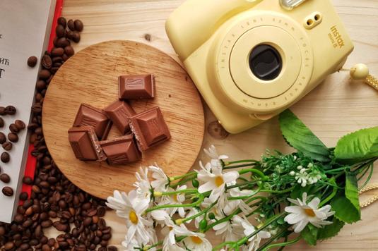 テイクアウトのコーヒーを片手に、ビジネスバッグを携えてビルのエントランスから出たところのビジネスマン。スーツ姿。