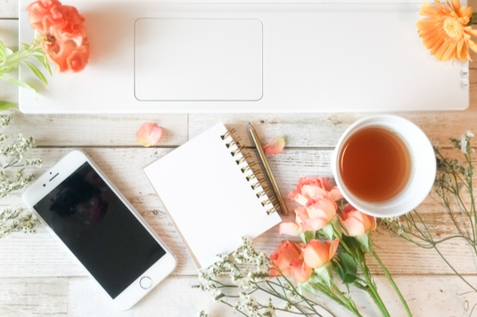 ノートパソコンの前に置かれたスマホ、メモ帳、鉛筆、紅茶の入ったマグカップ。オレンジピンクのバラ、オレンジのデイジー。