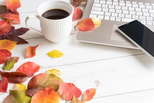 パソコンのキーボードとマウス。コーヒーの入ったマグカップ。水色のノートと手帳。トレイに置かれたメモ帳。マスキングテープ。白のバラ。