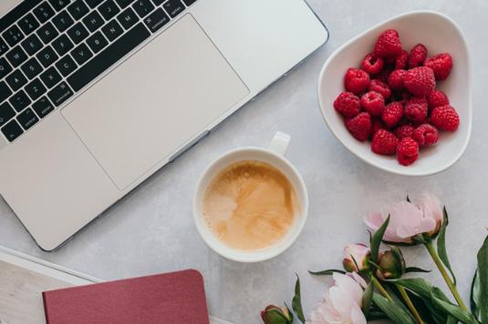ピンクの手帳の上に置かれたはさみ。ピンクの花型のティーカップ。ピンクのイヤフォン。