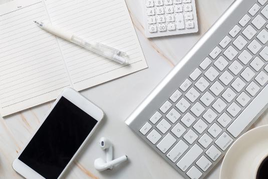 広げられたノートとボールペン。電卓、スマホとイヤホン、パソコンのキーボード、コーヒーカップ。