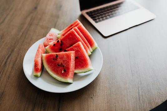 パソコンのキーボードとイヤフォン。メモ帳。ピンクのバラのブーケ。